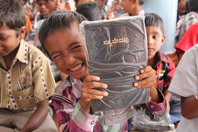 日本聖書協会の海外聖書支援先で聖書を手にして喜ぶ男の子(写真:日本聖書協会提供)