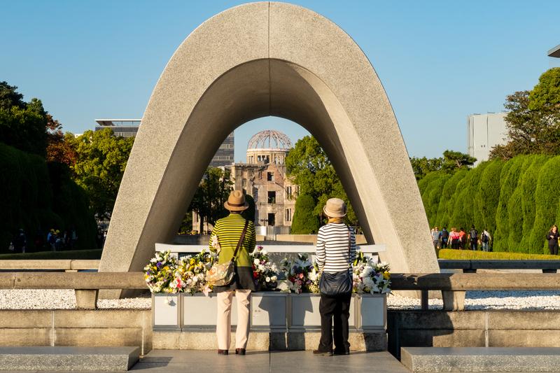 広島平和記念公園の原爆死没者慰霊碑前に立つ女性2人。慰霊碑の奥には原爆ドームが見える。=2019年10月31日(写真:Cleop6atra / Shutterstock.com)