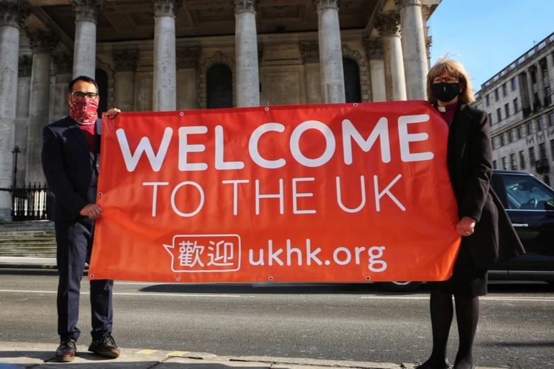 「英国へようこそ」と書かれた横断幕を持つ「UKHK」開設者のクリシュ・カンディア氏(左)と英国国教会ロンドン教区のサラ・マラリー主教(写真:UKHK)