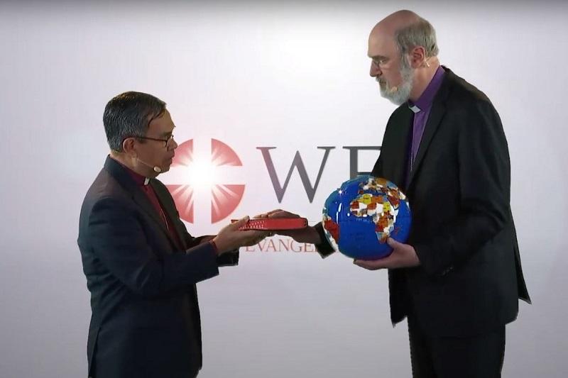 地球儀と聖書を世界福音同盟(WEA)のエフライム・テンデロ前総主事(左)から受け取るトーマス・シルマッハー新総主事(写真:WEA)
