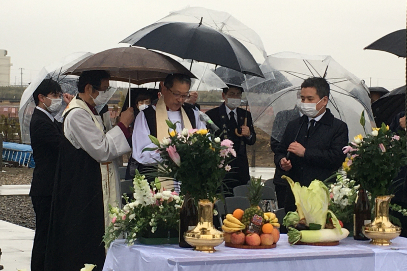 「荒浜記憶の鐘」の前で祈りをささげる日本聖公会の武藤謙一首座主教=13日、仙台市若林区で(写真:世界宗教者平和会議〔WCRP〕日本委員会提供)