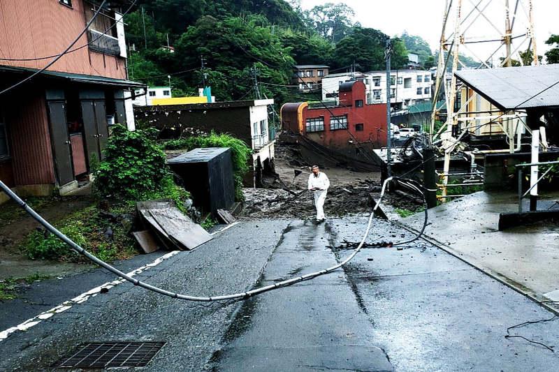 土石流で大きな被害を受けた熱海市伊豆山の般若院付近=4日。中央に立っているのが神戸国際支縁機構の岩村義雄理事長(写真:同機構提供)