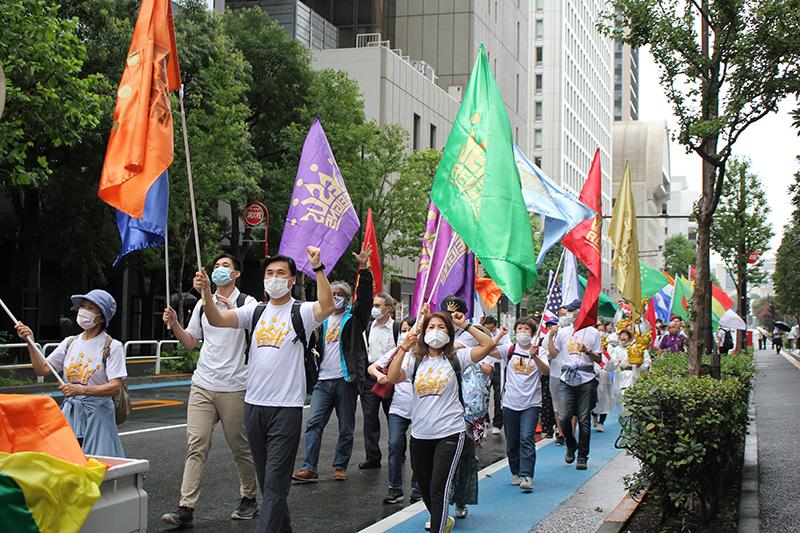 ジーザス・レインズのロゴマークの入った旗や世界各国の国旗を手に銀座の街を練り歩く参加者たち=13日