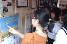 飢餓問題について説明する日本国際飢餓対策機構(JIFH)スタッフと説明を聞く若者