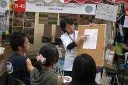 活動の説明をするチャイルド・ファンド・ジャパンのスタッフと話を聞く来場者