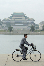 国指定の制服を来て自転車に乗る平壌市民<br />