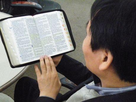 聖書を読む脱北者のスンさん(リリース・インターナショナル)。