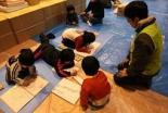 避難所で配布したスケッチブックに絵を描く子ども達