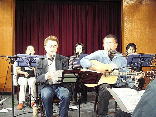 新曲「いつかきっと」を披露する岩渕まことさん(右)と演奏チーム=19日、お茶の水クリスチャン・センター(OCC、東京都千代田区)で