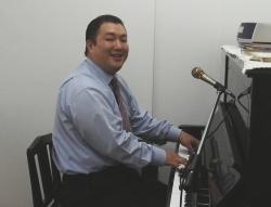 ピアノの腕を披露する新宿福興教会の菅野直基牧師