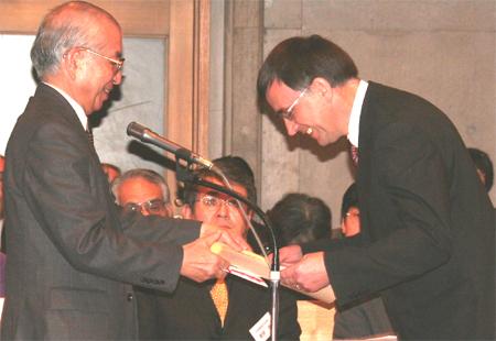 聖書事業功労者ロアルド・リーダル氏(右)に賞状を渡す聖書協会理事長、大宮溥氏(©JBS)