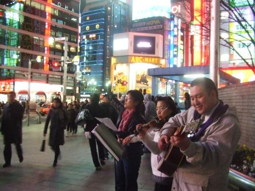 夜の新宿で主を力強く賛美する「ザ・ウェイ・オブ・グレイス」のメンバーと菅野直基牧師(13日午後6時53分、JR新宿駅アルタスタジオ前広場で)