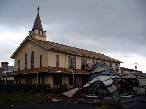 礼拝堂北側に衝突したプレハブはしばらくして風向きが変わると、強風で破損しながらさらに壁側に倒れ掛かってきた。(写真:嬉野キリスト教会提供)